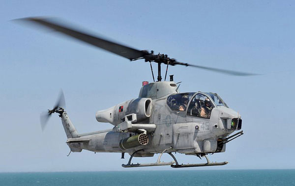 The AH-1W Super Cobra taking off is assigned to Marine Light-Helicopter Squadron (HMLA) 167 (Courtesy US Navy)