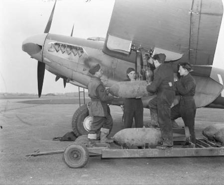 Armourers' hand-winch a 500-lb MC bomb to the wing loading-point on Mosquito FB Mark VI, MM403 'SB-V', of No. 464 Squadron RAAF at Hunsdon, Hertfordshire